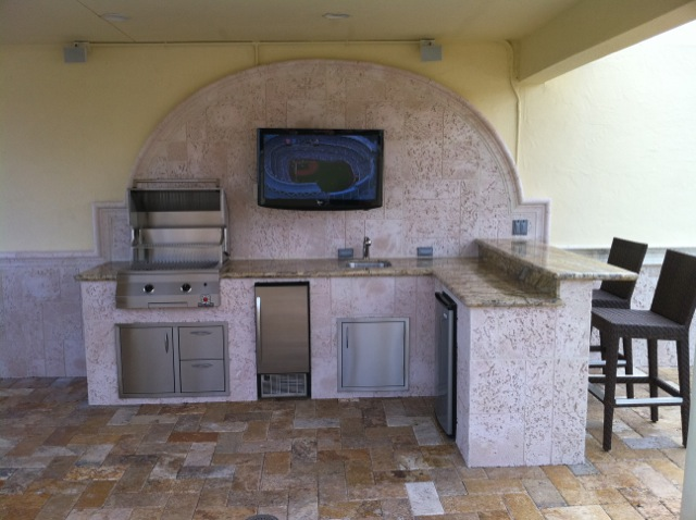 Outdoor kitchen with built in tv in coral back splash for Custom outdoor bbq kitchens