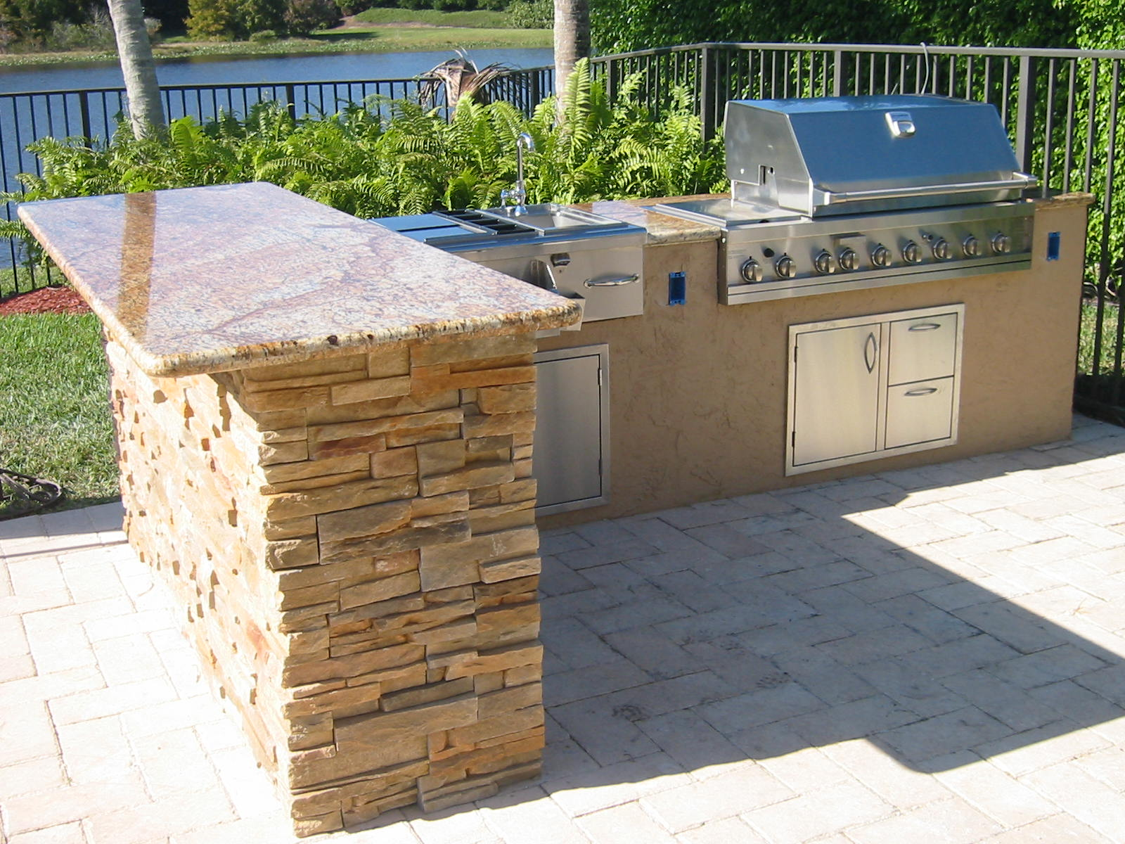 custom outdoor kitchen in florida with granite and ledge stone and bar