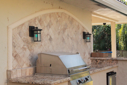 Custom outdoor kitchen with granite counter and marble for Outdoor kitchen backsplash ideas
