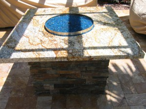 custom gas fire pit with granite top and blue fire glass
