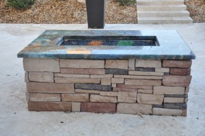 custom built fire pit with blue granite and stacked stone