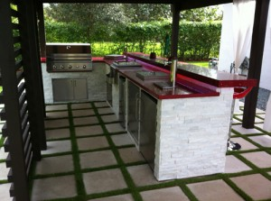 custom outdoor kitchen with red quartz counter top